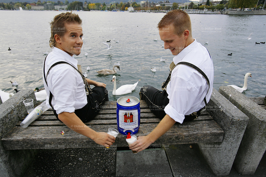 Switzerland. Canton Zürich. Zürich. Oktoberfest. Bier fair. Cheers, Your health. Two young men, seated on a wood and concrete bench close to the lake and wearing traditional leather clothes, are filling beer in their plastic glasses from an aluminium Feldschlossen barrel. The swans are swimming on the water.  © 2006 Didier Ruef