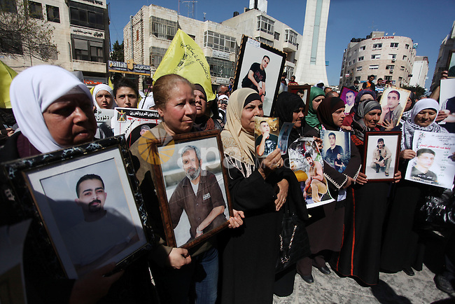 Palestinians carry portraits of prisoners in Israeli jails during a rally organized by the Ministry of prisoners in solidarity with Palestinian prisoners on hunger strike,in the West Bank city of Ramallah on February 27, 2013. Photo by Issam Rimawi