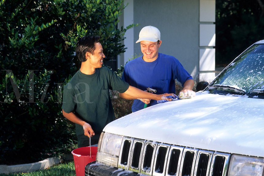 Affluent gay male couple having fun while washing their sport-utility vehicle car outside their home