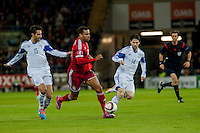 Wednesday 4th  December 2013 Pictured: Hal Robson-Kanu of Wales  makes his way past Marios Antoniades of Cyprus  and Vincent Laban  of Cyprus  <br /> Re: UEFA European Championship Wales v Cyprus at the Cardiff City Stadium, Cardiff, Wales, UK