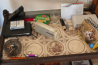 Switzerland. Canton Ticino. Sala. Various objets in the home of Elsy (Elsa) Hofer Ferrari Ramuz. On a small table in the living room, a telephone handset, a pack of Pall Mall cigarettes, a used astray with butts, a pen,  a Mac Iver can with sweet lemon candies, a small Sony radio, two watches, a calendar with a picture of a cat and a white open envelope. Pall Mall is an American brand of cigarettes produced by R. J. Reynolds Tobacco Company and internationally by British American Tobacco. Sony Corporation is a Japanese multinational conglomerate corporation with diversified business which includes consumer electronics. Elsy Hofer Ferrari Ramuz is the niece of Charles-Ferdinand Ramuz (September 24, 1878 – May 23, 1947) who was a French-speaking Swiss writer. 14.11.2017 © 2017 Didier Ruef