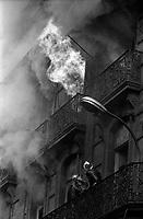 """Edifice commercial et de bureaux, magasin """"Au gaspillage"""" au début du XXe siècle, """"Au bon marché de Paris, """"le Printemps"""" et les assurances """"Le continent"""" dans les années 1960, """"Bouchara"""", """"Zara"""", 47 rue d'Alsace-Lorraine. 11 Mars 1964. Vue de l'incendie de l'immeuble du Printemps et de l'intervention des pompiers : vue prise en hauteur d'un immeuble en face ; l'immeuble ravagé par le feu, entouré de nuages de fumée épaisse, des flammes sortent d'une fenêtre du troisième niveau, sous le regard de deux pompiers juste en dessous sur un balcon."""