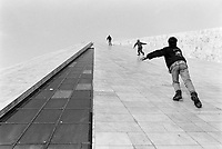 """Albania. Tirana. Three teenagers run up the slopes of the Pyramid to get to the top of the building. The Pyramid, also called International Center of Culture, is a structure and former museum that opened on October 14, 1988, formerly known as the """"Enver Hoxha Museum"""". Its angled shape structure vaguely reminiscent of a pyramid was designed by the daughter and son-in-law of the late communist leader Enver Hoxha. It was originally intended to be a mausoleum and museum for the country's deceased leader Enver Hoxha. It served as a museum about his legacy. Then came in 1991 the collapse of communism. Albania's transition from isolated Stalinist state to aspiring member of the EU has been reflected in the fortunes of Tirana's pyramid. In 1991, the building was renamed in honor of persecuted activist Pjeter Arbnori and became a conference center and exhibition venue. During the 1999 conflict in Kosovo, NATO set up a humanitarian headquarters inside the pyramid. In 2001, Albanian television station Top Channel moved in. In 2010, the Albanian government decided to raze the pyramid and build a sleek new parliament building in its place. The pyramid, however, still stands. Though many would like to destroy the specter of communist rule, a vociferous group Albanian intellectuals, activists, and even former political prisoners of Hoxha are in favor of its preservation. Ther argument: history, no matter how dark or ugly, must be remembered. As debate continues (2016), the pyramid sits dilapidated and vandalized, awaiting an uncertain future. Tirana is the capital and largest city of Republic of Albania. 24.11.1998 © 1998 Didier Ruef"""