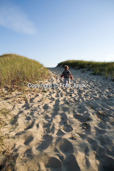 Young Boy walks towards sand dunes on South Beach in Marthas Vineyard in Edgertown, MA, USA