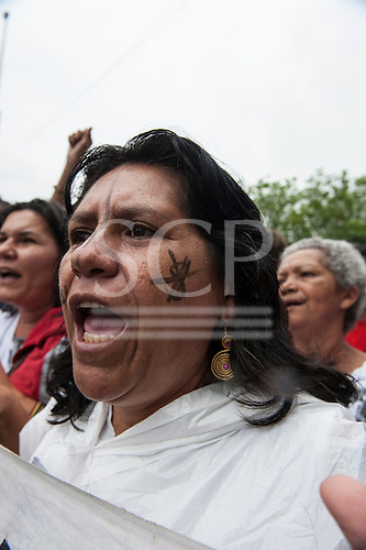 A demonstrator with a crossed out dollar symbol painted on her cheek chants at a demonstration by indigenous people, the Landless People's Movement (MST) and other civil society groups in front of the Riocentro United Nations conference. The demonstrators are kept out of earshot and invisible to the UN conference. The United Nations Conference on Sustainable Development (Rio+20), Rio de Janeiro, Brazil, 20th June 2012. Photo © Sue Cunningham.