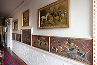 Painted hunting scenes, framed by delicately wrought plaster moulding, run the length of this corridor