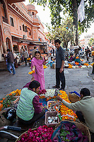 Jaipur, Rajasthan, India.  Woman Buying Marigolds before Entering a Hindu Temple.