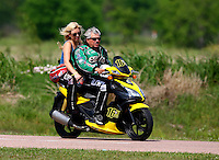 Apr 25, 2014; Baytown, TX, USA; NHRA funny car driver John Force (right) rides a scooter with daughter Courtney Force during qualifying for the Spring Nationals at Royal Purple Raceway. Mandatory Credit: Mark J. Rebilas-USA TODAY Sports