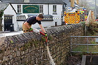 Pictured: A fireman leads handles the end of a hose.<br /> Re: Cleanup after storm Dennis in Crickhowell, Wales, UK.