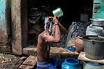 A boy bathes in open at Maniktola slum in Kolkata during 21 days lock down in India due to covid 19 pandemic. Kolkata, West Bengal, India. Arindam Mukherjee.