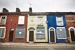 Derelict housing in the colours of the city's two football clubs behind Anfield stadium, home of Liverpool football club. Photo by Colin McPherson.