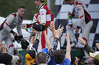 #9: Pfaff Motorsports Porsche 911 GT3R, GTD: Zacharie Robichon, Laurens Vanthoor, #1: Paul Miller Racing Lamborghini Huracan GT3, GTD: Madison Snow, Bryan Sellers, #14: Vasser Sullivan Lexus RC F GT3, GTD: Jack Hawksworth , Aaron Telitz celebrate on the podium with champagne as fans jump for hats