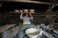 Japan, Mie Prefecture, Iga City. Family run Iga pottery studio, at least eight generations. Iga pottery is a special style using local hard clay with a high resistance to fire. The daughter is at least eighth generation and learned from her father, at the potters wheel. She's the youngest of four girls, but only two of them do pottery. It's a male oriented profession as the kneading is very physical. She stayed at a Zen monsatery for a year, and studied spiritual training as well as cooking school to apply these skills to her earthenware pottery. She finds making pottery very meditative and likes to imagine the food cooking in her pot as she's making it. Model released