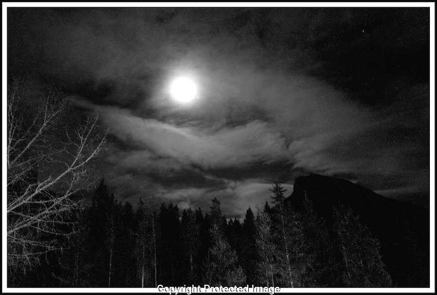 Black and white shot of the moon seen through the clouds in Banff Alberta
