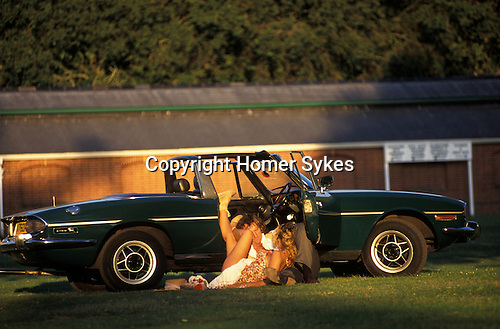 Ascot, Berkshire. 1990s<br /> In the exclusive Number 1 Car Park at Royal Ascot leaning up against his racing green Triumph Stag in the late afternoon summer sun, a couple celebrate a win on the runners or perhaps just celebrate by getting down to some serious foreplay after a bottle or two of lunch time picnic bubbly