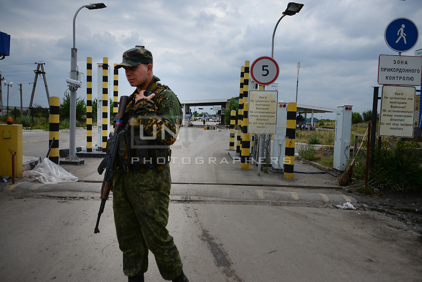 Rebel soldier patrolling the border between Ukraine and Russia at Izvarine check point - one of border crossings controlled by Luhansk Peoples republic