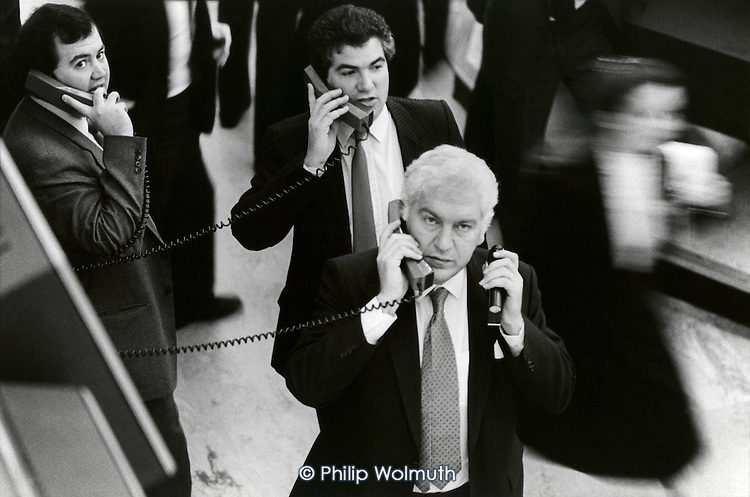 Dealers on the floor of the London Stock Exchange resort to telephones when new technology fails on the day of the 'Big Bang' deregulation of financial services by the Thatcher government.