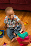 21 month old toddler boy playing with stacking cardboard blocks, putting toy vehicle on top of stack
