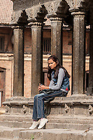 Nepal, Patan.  Young Nepalese Woman in Western Clothes Holding Cell Phone.