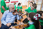 © Joel Goodman - 07973 332324 . 27/09/2016 . Liverpool , UK . Labour Party leader JEREMY CORBYN is shown how to play the violin by JESSICA KELLY (10) during a visit to Faith Primary School in Liverpool , where he listens to and then joins in with the school orchestra . Photo credit : Joel Goodman