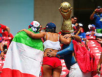 Italy fans pose for a photograph with a Costa Rica fan wearing short shorts