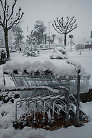 Switzerland.  Canton Ticino. Lugano, Winter season. Row of shopping trolleys during snow blizzard. Fresh snowfall on shopping carts parked outside the Migros Supermarket. Migros is Switzerland's largest retail company, its largest supermarket chain and largest employer. A man walks on the sidewalk while holding an umbrella. 28.12.2020 © 2020 Didier Ruef