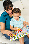21 month old toddler boy at home with mother both driving toy cars across map in book