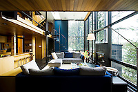 Wall panels painted alternately blue or red are picked up in accessories and soft furnishings, illustrated in the living area in the occasional blue sofa cushion