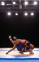 11 DEC 2011 - LONDON, GBR - Krasimir Krastanov (GBR) (in red) throws Qi Mude (CHN) (in blue) during their 55kg category bronze medal bout at the London International Wrestling Invitational and 2012 Olympic Games test event at the ExCel Exhibition Centre in London, Great Britain (PHOTO (C) NIGEL FARROW)