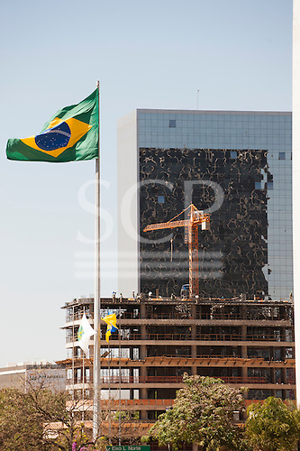 Brasilia, Brazil. New building under construction with the Brazilian flag and an older completed building with mirror glass front. Workers on the top floors and a construction crane.