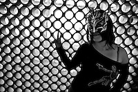 """A female Lucha libre wrestler Sexy Polvora poses for a picture before a fight at a local arena in Mexico City, Mexico, 29 April 2011. Lucha libre, literally """"free fight"""" in Spanish, is a unique Mexican sporting event and cultural phenomenon. Based on aerial acrobatics, rapid holds and the use of mysterious masks, Lucha libre features the wrestlers as fictional characters (Good vs. Evil). Women wrestlers, known as luchadoras, often wear bright shiny leotards, black pantyhose or other provocative costumes. Given the popularity of Lucha libre in Mexico, many wrestlers have reached the cult status, showing up in movies or TV shows. However, almost all female fighters are amateur part-time wrestlers or housewives. Passing through the dirty remote areas in the peripheries, listening to the obscene screams from the mainly male audience, these no-name luchadoras fight straight on the street and charge about 10 US dollars for a show. Still, most of the young luchadoras train hard and wrestle virtually anywhere dreaming to escape from the poverty and to become a star worshipped by the modern Mexican society."""