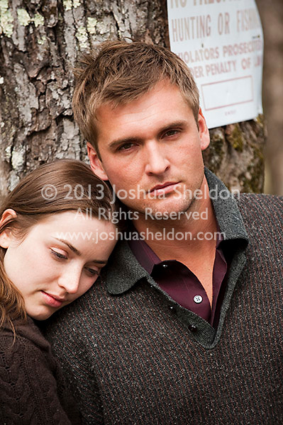 Young couple leaning on tree, man looking at camera