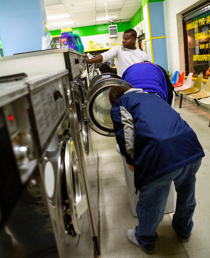 Mae Gammino/Warwick Beacon<br /> <br /> Ray, foreground, and Kevin, center, receive help from a staff member while they do their laundry.  Each has a different degree of abilities; Kevin needs help with every aspect of a daily routine, while Ray's need is more basic.  They have been roommates for over 3 years, and have become close with their social workers whom they consider family.