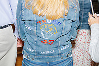 "A woman wears a jean jacket embroidered with the likeness of US president Donald Trump and the slogan ""Keep America Great"" while people gather for a Trump campaign office opening party in Salem, New Hampshire, on Fri., Sept. 18, 2020. Former 2016 Trump campaign manager and current 2020 Trump campaign senior advisor Corey Lewandowski, lives in nearby Windham, NH, spoke at the event, which also doubled as a surprise birthday celebration for Lewandowski."