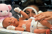 Nurse attends premature infant in an incubator in neonatal intensive care unit (NICU)