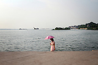 A woman walks on the shore of Dongting Lake, Hunan Province. Dongting Lake has decreased in size in recent decades as a result of land reclamation and damming of the Yangtze. China. 2010