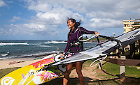 A windsurfer carries her windsurfing board towards the ocean at Ho'okipa Beach, Maui.