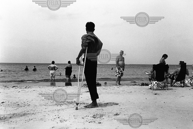 Myo Myint takes a walk along the beach on Lake Michigan, Indiana. At 16 Myo joined the army of the ruling Burmese junta, where he lost his right forearm and lower leg whilst laying a mine. The blast also took away his left eye and most of the fingers on his left hand. It was while recovering from his injuries in hospital that Myo Myint made the life altering and dangerous decision to change sides. He joined the new democratic opposition, a choice that would lead to a total of 15 years spent in prison. The documentary 'Burma Soldier' follows Myo Myint's journey from refugee camp on the Thai-Burma border to eventually being re-united with his siblings in the United States, chronicling his transformation from a soldier of Burma's junta to democracy activist; from a political prisoner to a refugee in a foreign land.