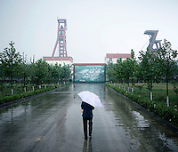 A woman walks under an umbrella in the rain as she walks towards a coal mine in Shanxi Province.