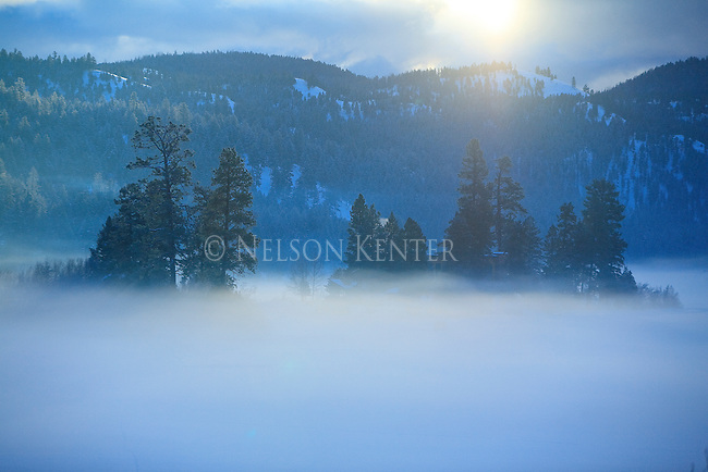 A layer of fog hugs the ice above Salmon Lake in mid winter in Montana