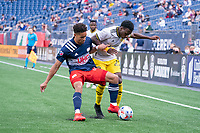FOXBOROUGH, MA - MAY 16: Brandon Bye #15 of New England Revolution tackles Derrick Etienne Jr. #22 Columbus SC during a game between Columbus SC and New England Revolution at Gillette Stadium on May 16, 2021 in Foxborough, Massachusetts.