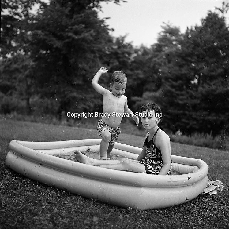 Bethel Park PA:  Michael Stewart sneaking up on his big sister Cathy in the relatively new and used Bakelite swimming pool.