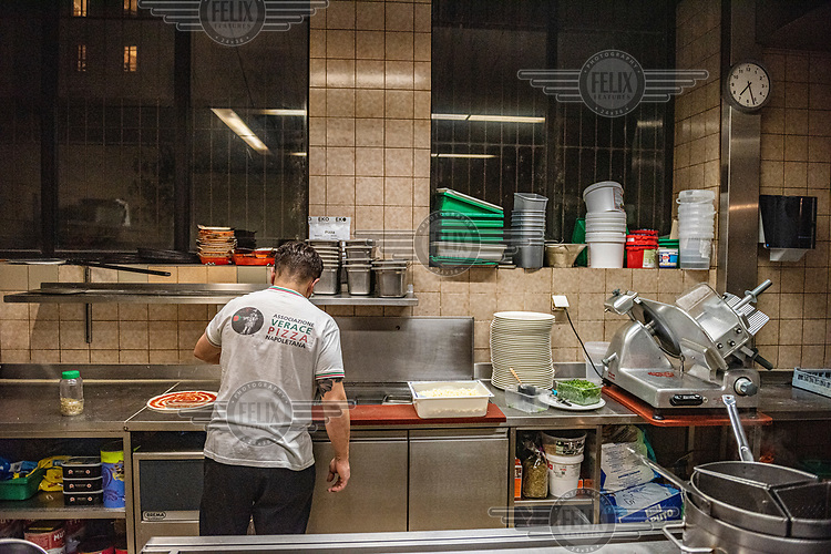 Andriulo prepares a pizza for take away as he works alone in his restaurant's kitchen during Geneva's second lockdown. Restaurants have been permitted to stay open, but only for take away service. Andriulo has had to lay off his staff and is attempting to pay some of the bills and the rent with earnings from a take away service and discounting pizza prices.