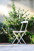 A white garden chair on gravel and green plants on the wall in afternoon warm sunshine Clos des Iles Le Brusc Six Fours Cote d'Azur Var France