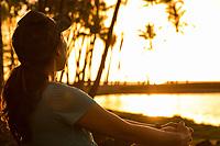 A woman looks towards Ku'uali'i Fishpond and the ocean at sunset, 'Anaeho'omalu Bay, Big Island of Hawai'i.