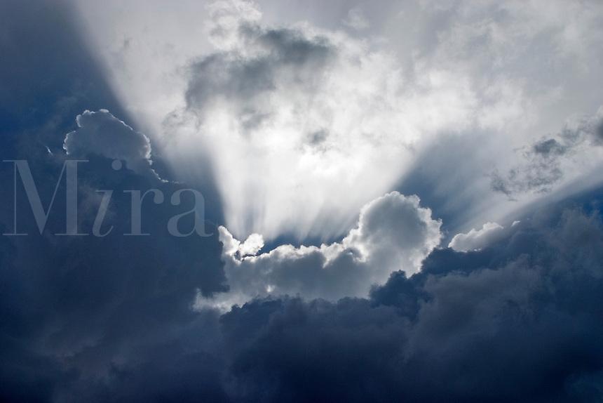 Sunburst.  Sun's rays bursting between layers of cumulus and heavy rain cloud..