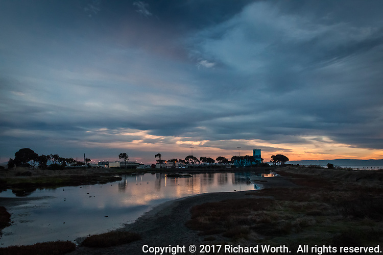 An overcast sky at sunset reflects in a fresh water pond dotted with a variety of waterfowl north of a water treatment plant, both are on the eastern side of the  San Francisco Bay Trail, on the western side is the Bay.