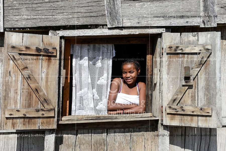MADAGASCAR, Mananjary, ANTAMBAHOAKA tribe, village AMBOHITSARA, girl looking out from window of wooden hut / MADAGASKAR, Mananjary, Stamm der ANTAMBAHOAKA, Dorf AMBOHITSARA am canal des Pangalanes, Maedchen blickt aus dem Fenster einer Holzhuette