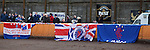 Rangers fans drape their flags over the speedway track