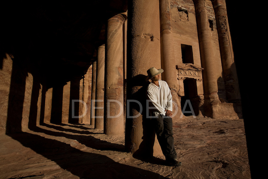 A male tourist wearing a hat stands near the entrance to the Um Tomb in the Nabatean ancient city of Petra, Jordan.